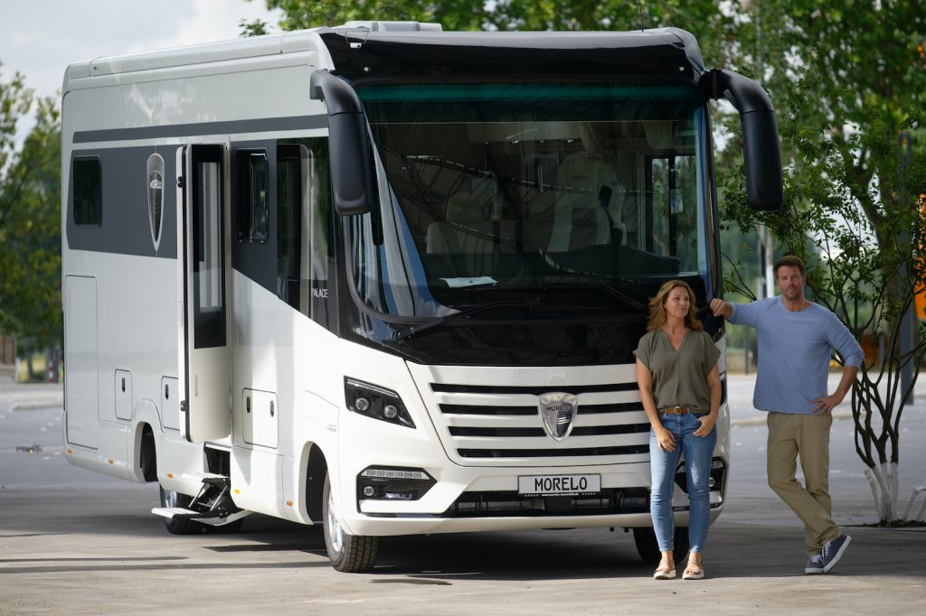 Two models are standing in front of the Morelo Palace 90 SE motorhome RV