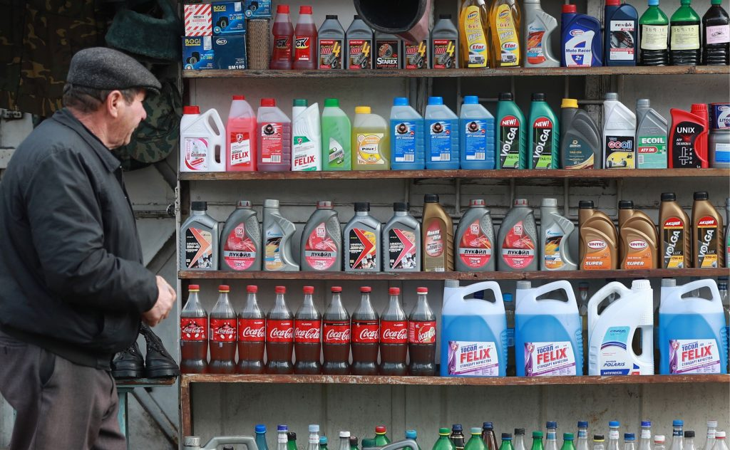 Bottles of different coolant colors on shelves, along with oil and other automotive fluids