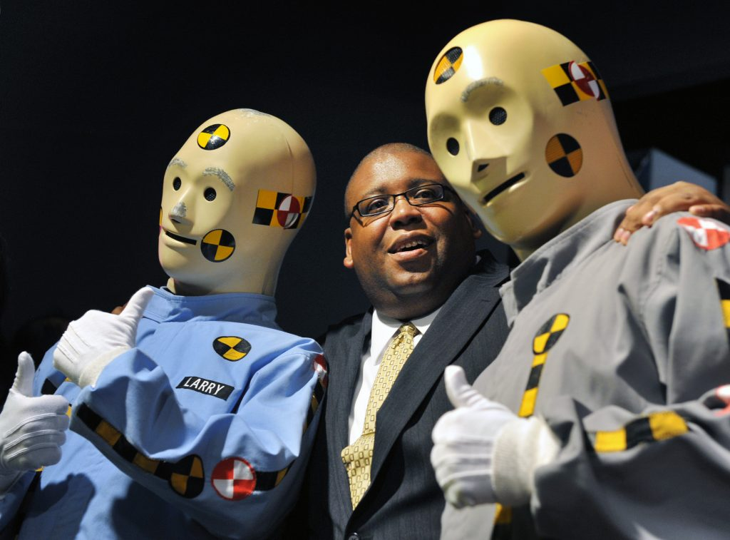 An NHTSA employee poses with the crash test dummies.