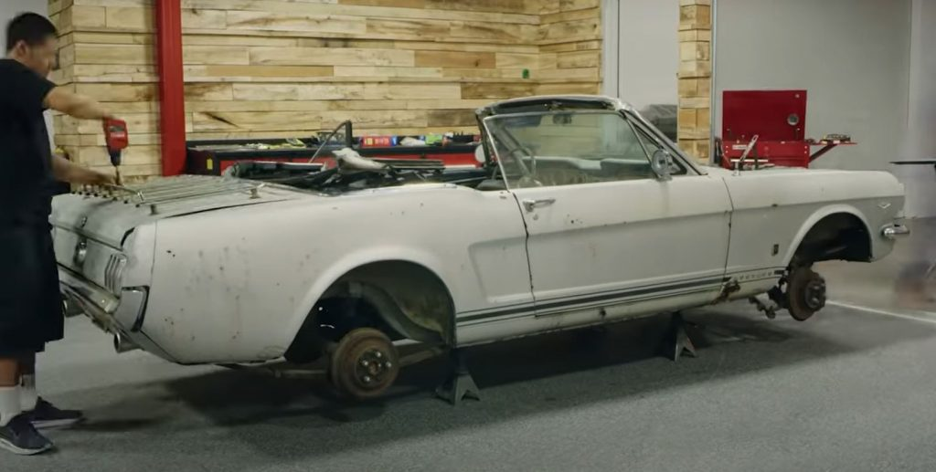 The shell of a 1965 Ford Mustang sits on tower jacks in a shop.