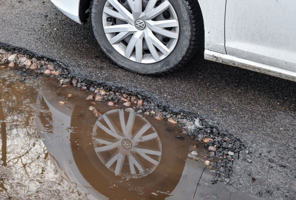 28 January 2019, Brandenburg, Briesen: The car tyre of a Volkswagen can be seen on a defective asphalt road surface and is reflected in a puddle. Photo: Patrick Pleul/dpa-Zentralbild/ZB (Photo by Patrick Pleul/picture alliance via Getty Images)