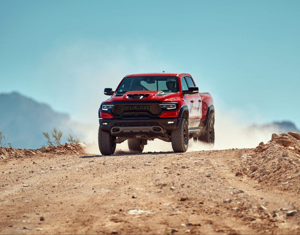 a red Ram 1500 TRX at speed on a dusty desert trail