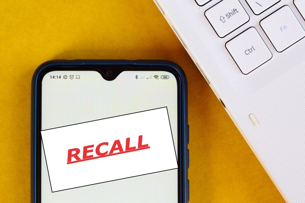 The word, RECALL, is seen displayed on a smartphone.