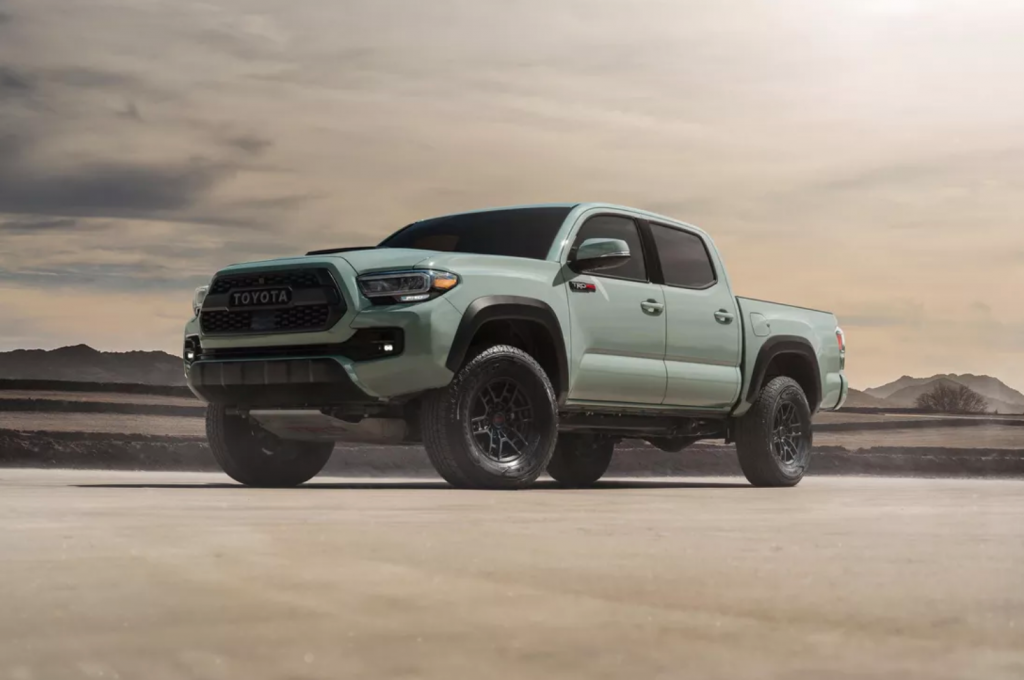 A 2021 Toyota TRD Pro Tacoma parked on sand is smaller than larger off-road options like the Ram 1500 TRX