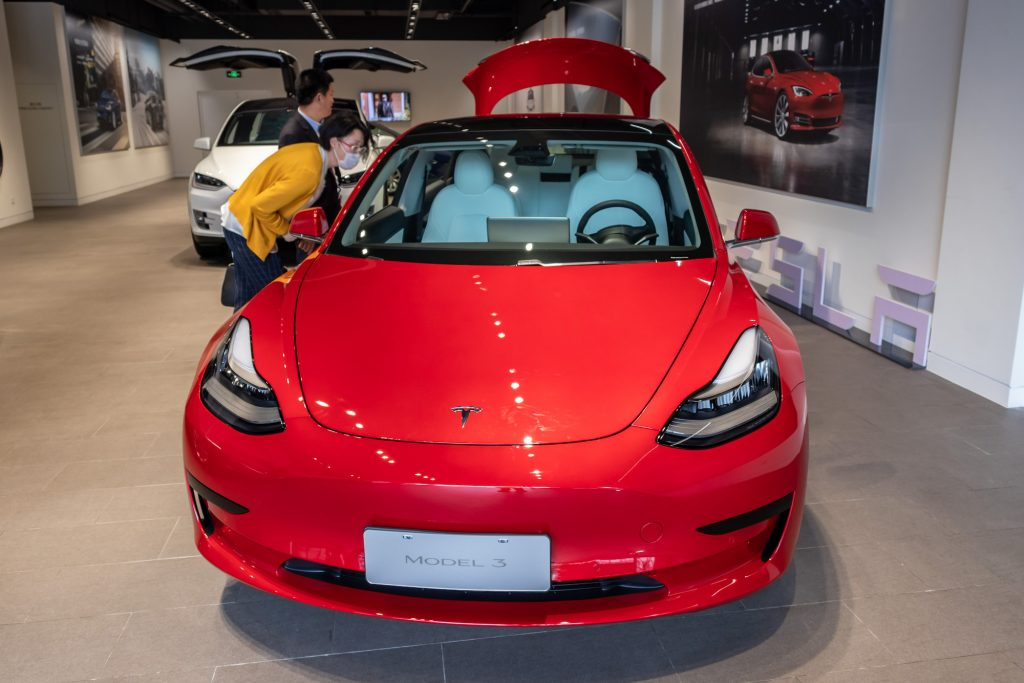 People look at a Tesla Model 3 car at the first Tesla Center in Shanghai