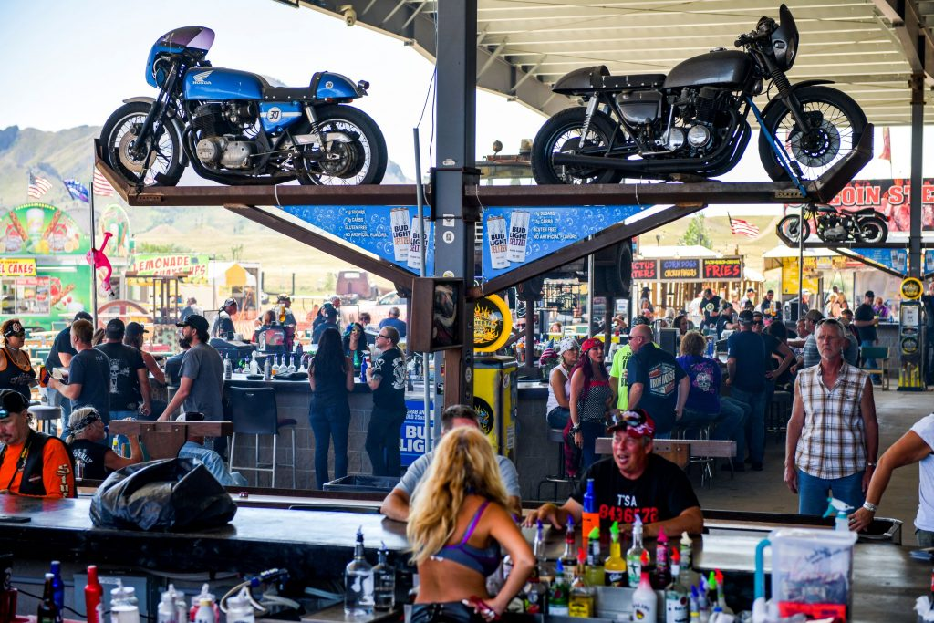 People sit at the outdoor bar of the Full Thottle Saloon during the 80th Annual Sturgis Motorcycle Rally.