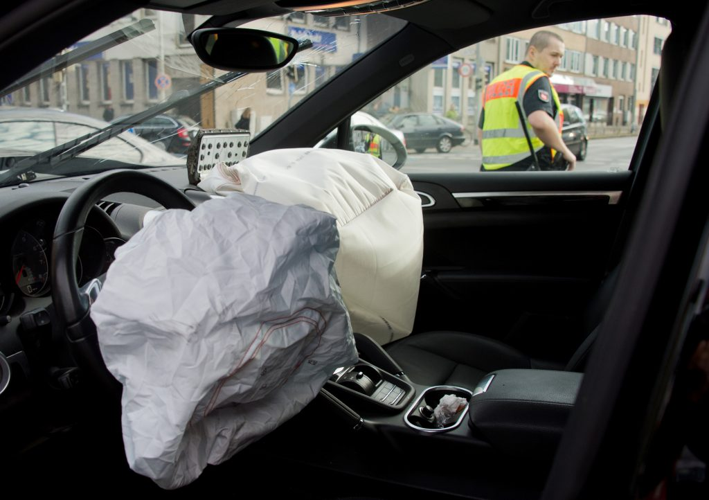 A police officer can be seen through the window of a car that has had two front airbags depoloyed.