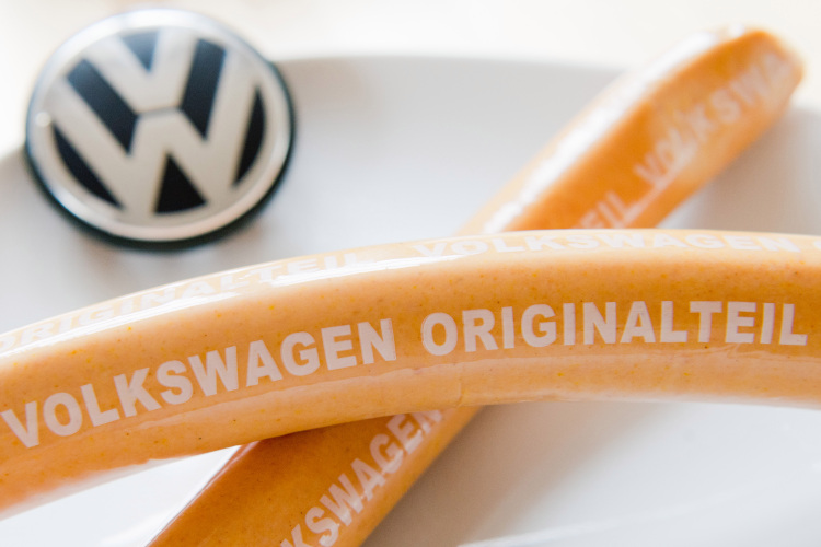 Curry sausages with 'Volkswagen Originalteil' lying on a kitchen table.