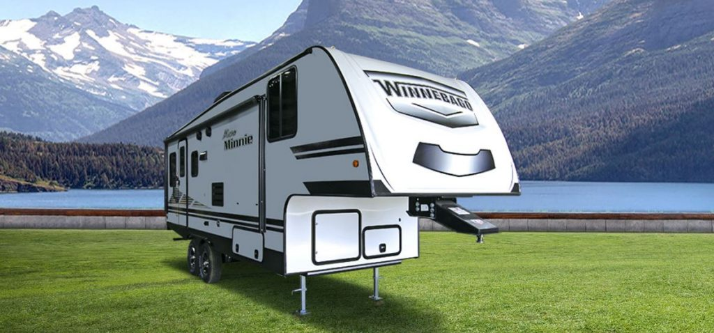 A white fifth wheel trailer is set in a snow-capped valley with a lake behind it.