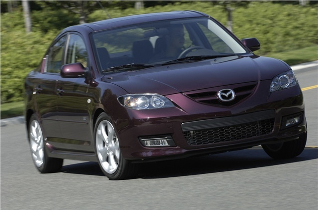 2008 Mazda3 in a purple color driving on the road
