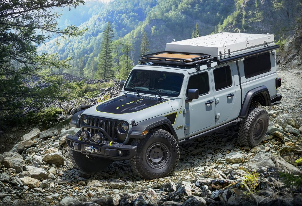 A gray Jeep Gladiator pickup is going down a trail road.