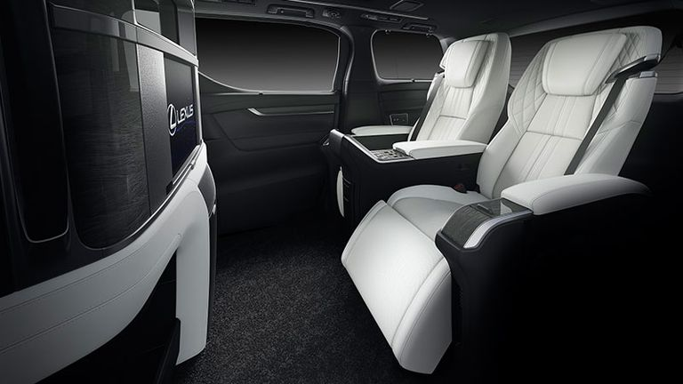 executive recliner seats in white leather in front of an impressive touch screen display