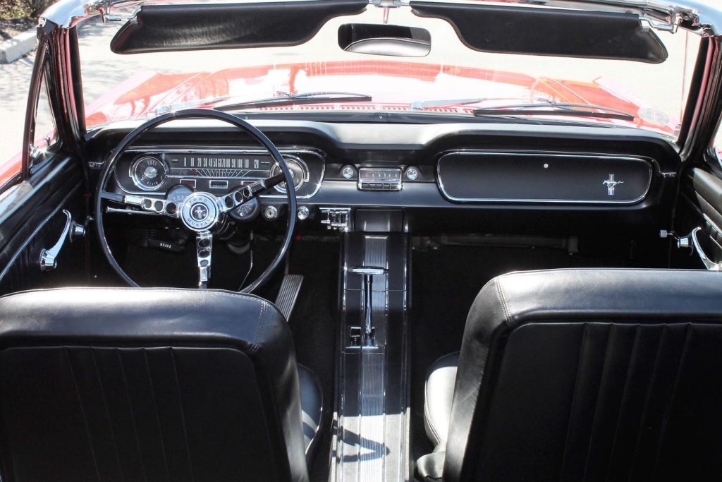 The black interior of a classic Ford Mustang is viewed from above the rear while the top is down.