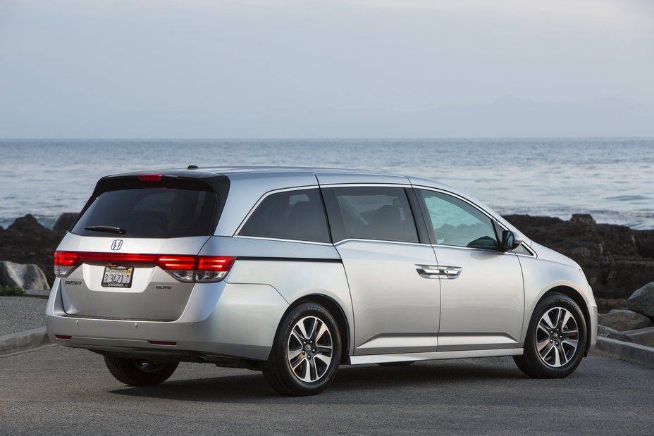 rear view of a silver 215 Honda Odyssey minivan parked near the shore