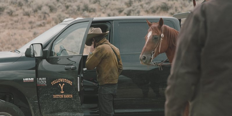 Yellow stone ranch truck with the door open and a cowboy leading his horse as he reaches in to get something form the cab.