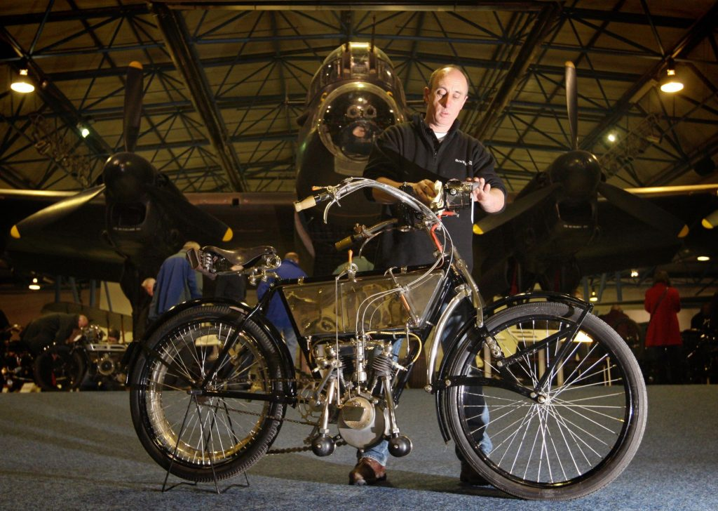A 1905 Peugeot 3.5-hp V-twin motorcycle being photographed in front of an old airplane