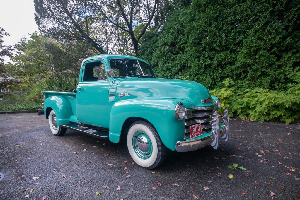 A teal 1951 Chevy 3100 truck on a hedge-lined driveway