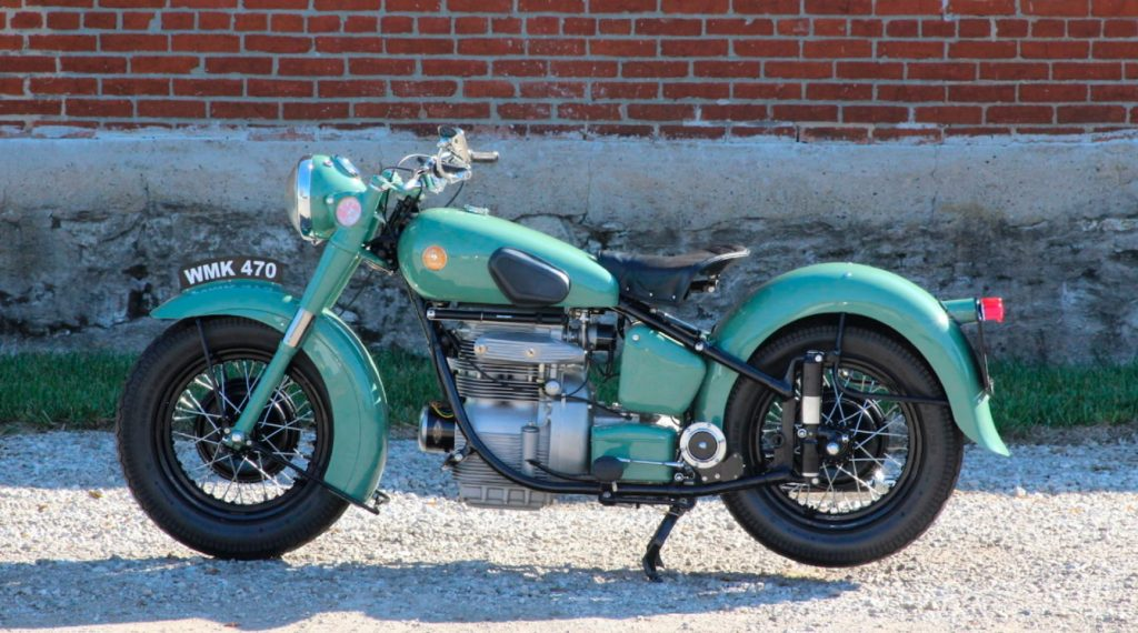 A turquoise 1951 Sunbeam S7 Deluxe in front of a brick wall