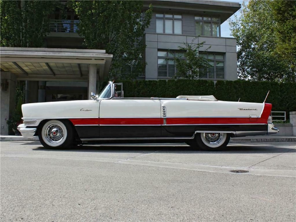 The side view of a white-red-and-black 1955 Packard Caribbean convertible