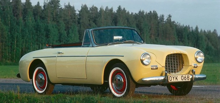 A yellow 1956 Volvo P1900 convertible in front of a forest