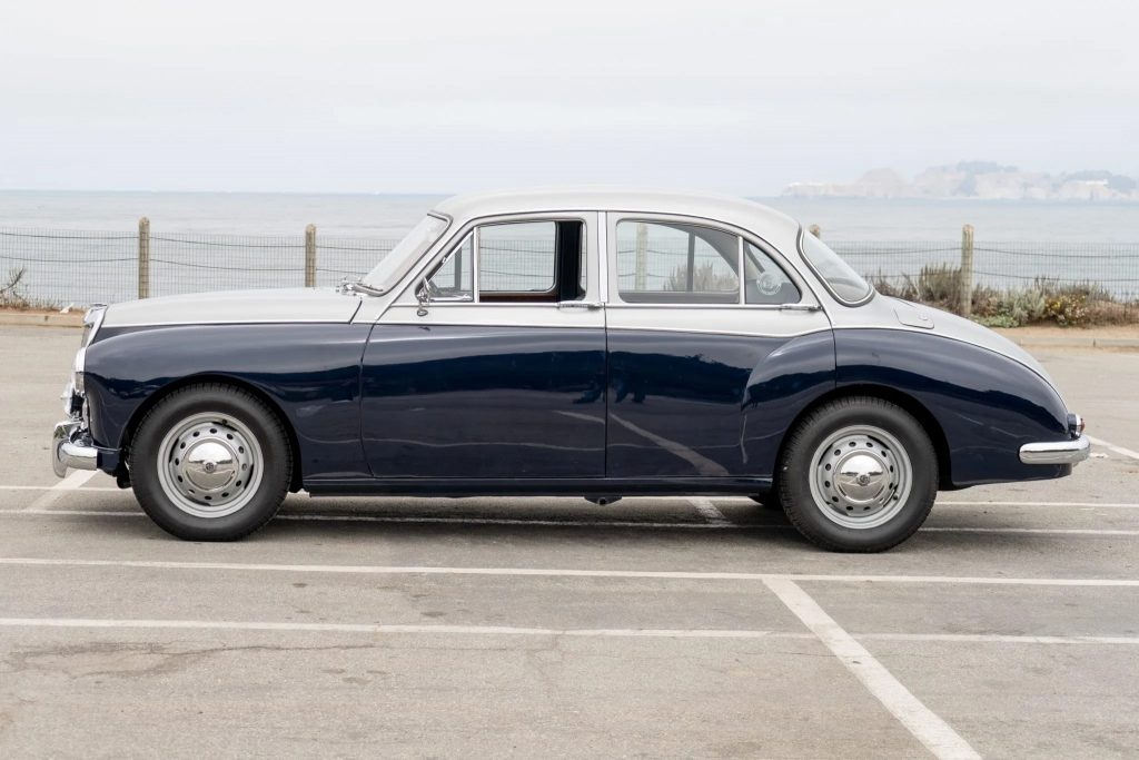 The side view of a blue-and-silver 1958 MG Magnette ZB Varitone by the sea