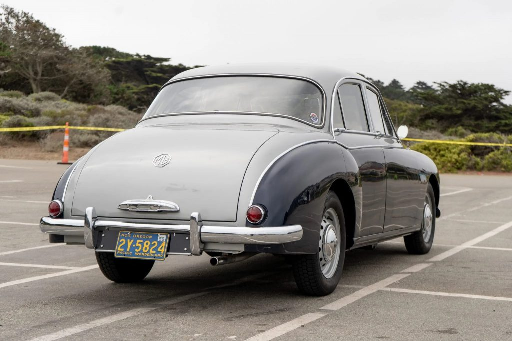 The rear view of a blue-and-silver 1958 MG Magnette ZB Varitone by a beach