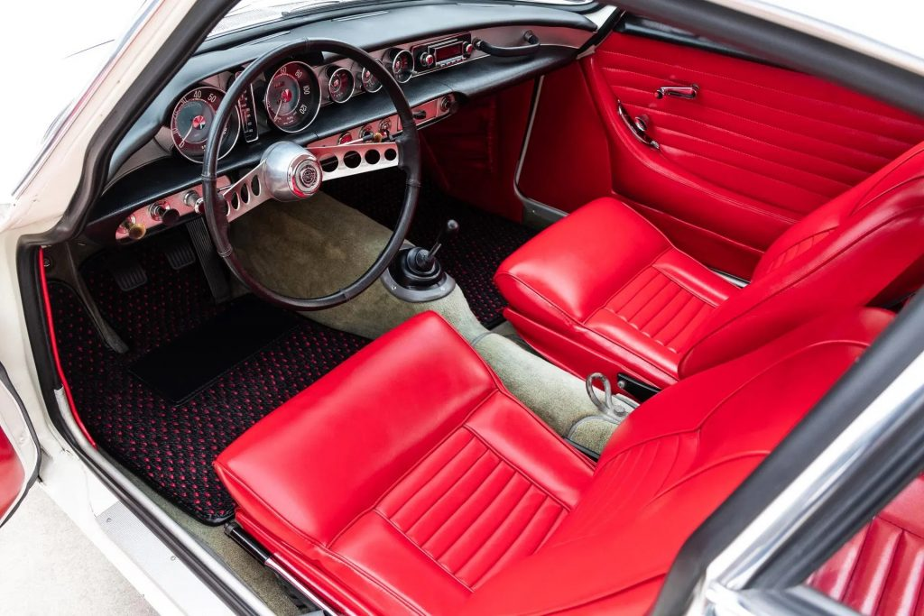 The red-leather interior of a white 1964 Volvo P1800S