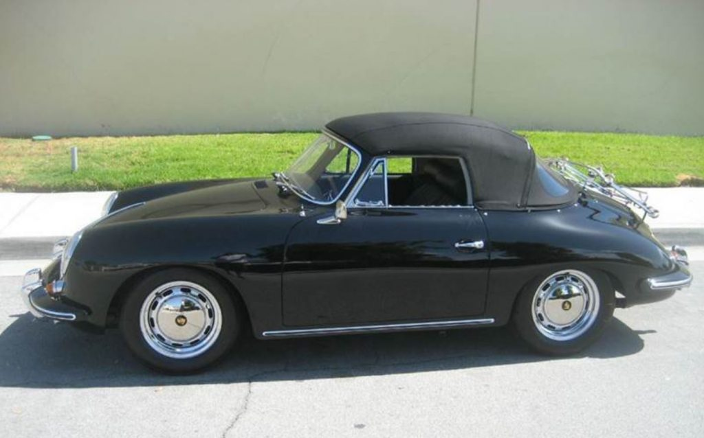 A black 1965 Porsche 356 SC Cabriolet sit by a curb with its black convertible top up.