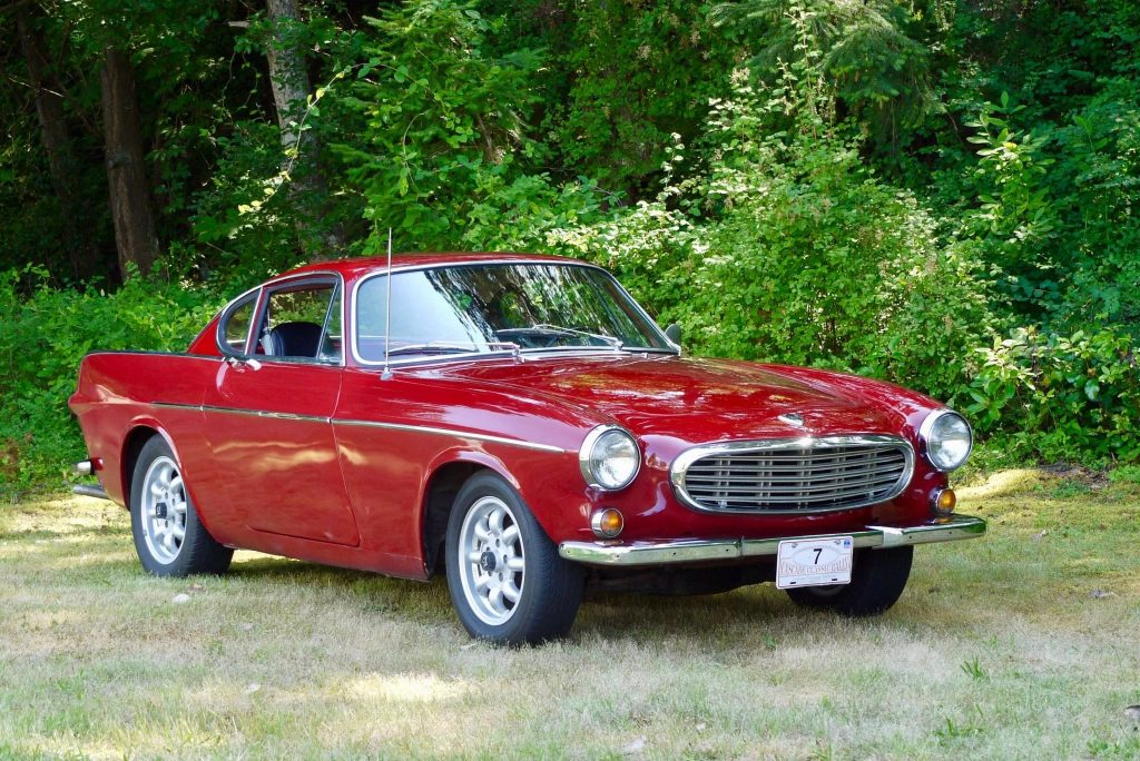 A red 1967 Volvo P1800S in front of a forest