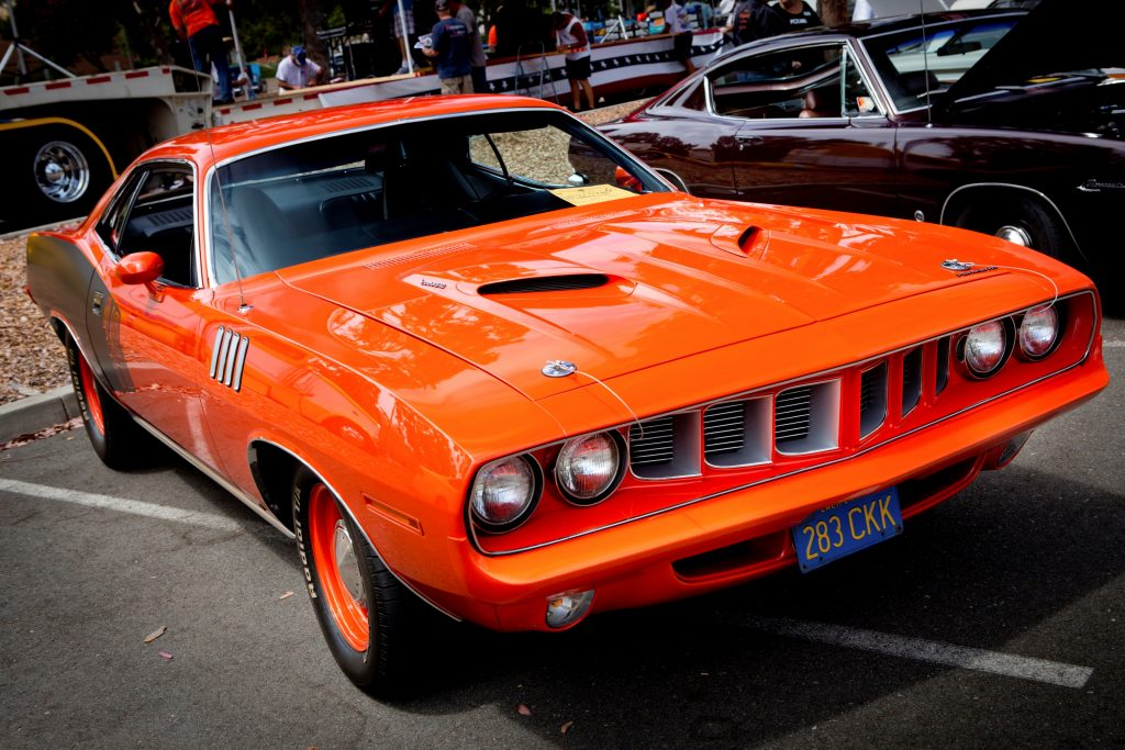 A classic red Plymouth Barracuda muscle car is viewed from the passenger front quarter side.