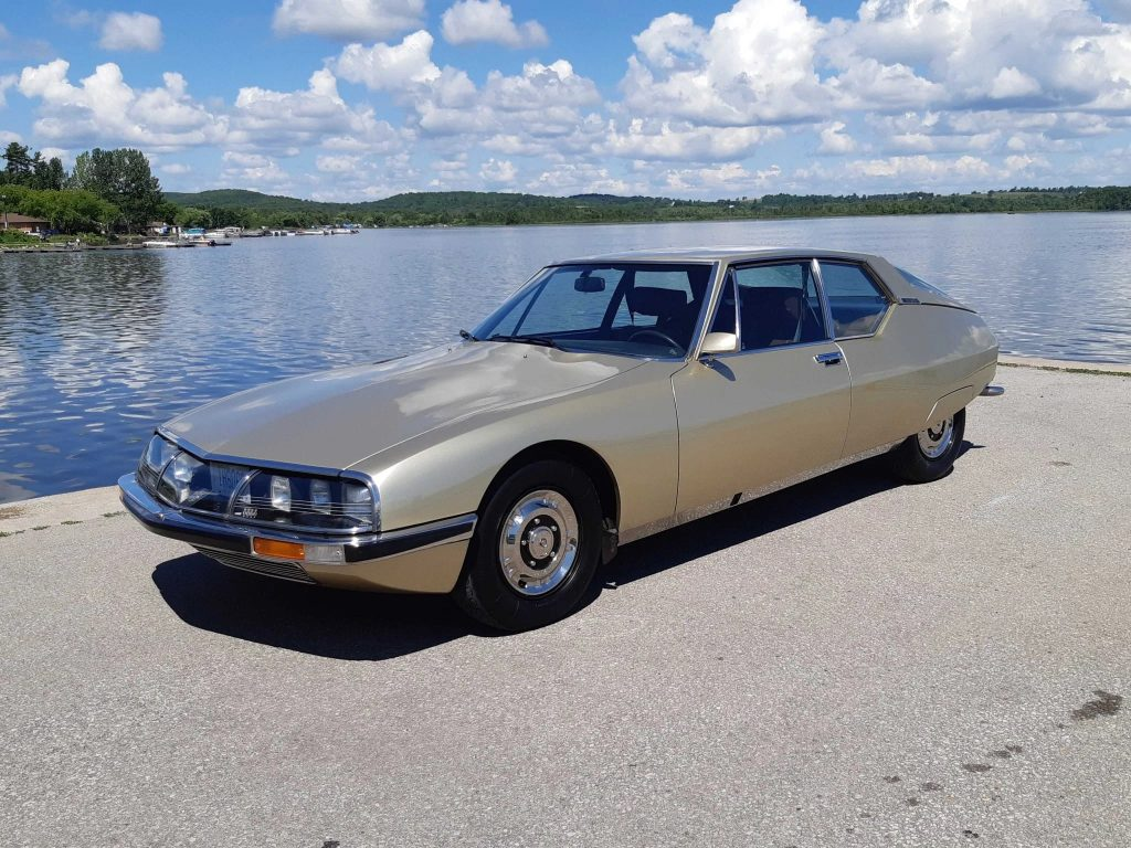 A gold 1972 Citroen SM in front of a lake