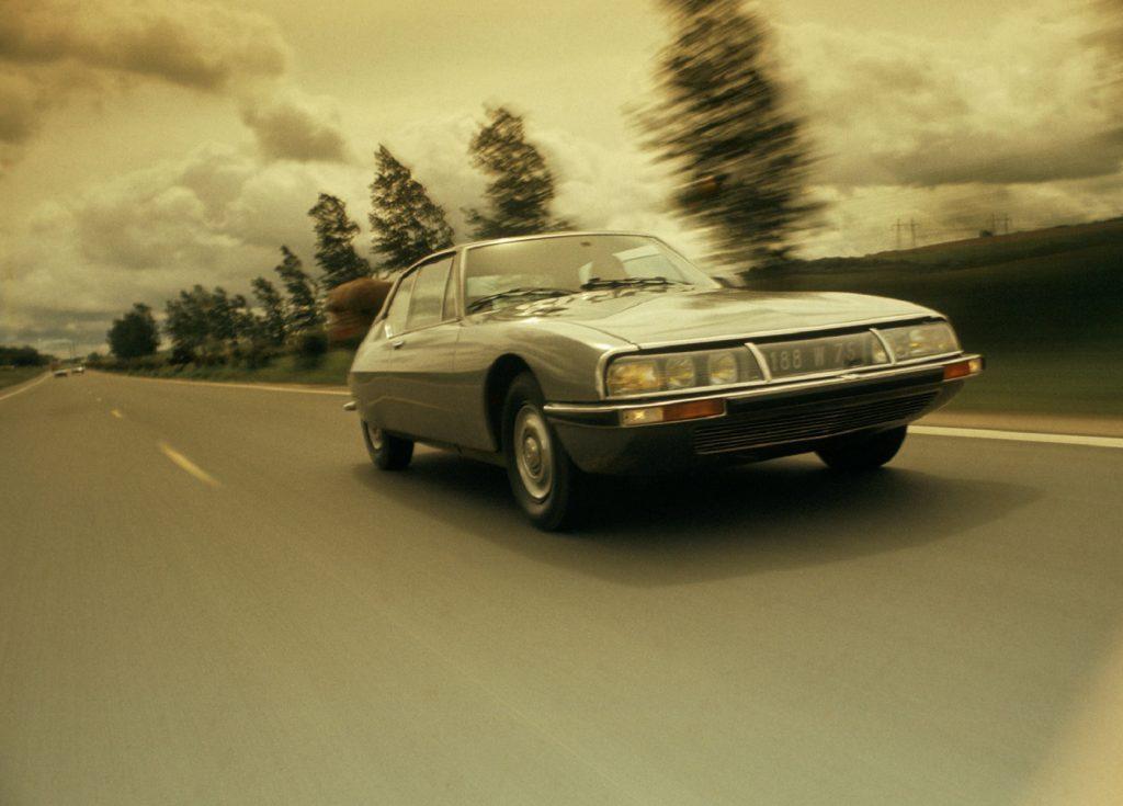 A gray 1972 Citroen SM drives down the road