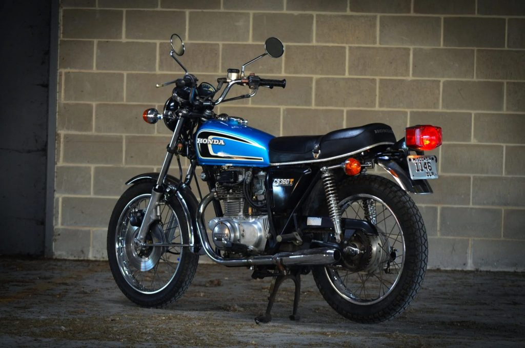 The rear 3/4 view of a blue 1975 Honda CB360T in a parking garage