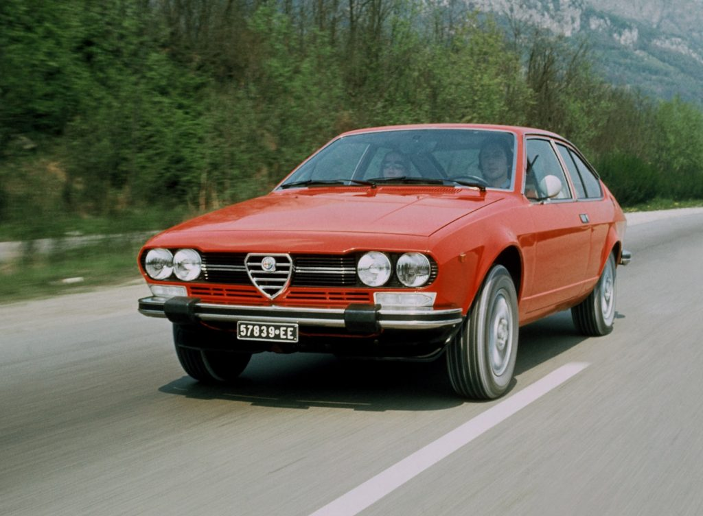 A red 1976 Alfa Romeo GTV 2.0 drives down a mountain road