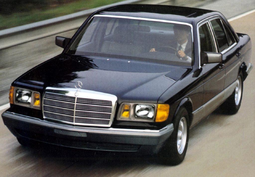 A black 1979 Mercedes-Benz W126 S-Class drives down the road