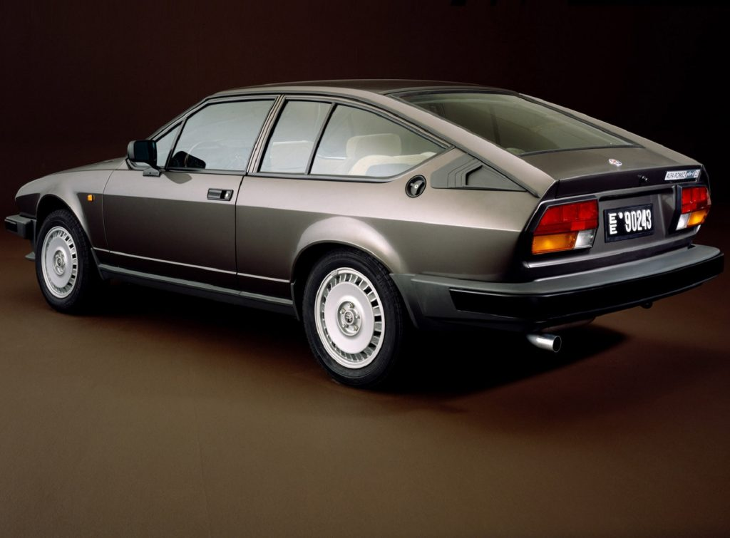 The rear-3/4 view of a gray 1980 Alfa Romeo GTV6 against a brown background