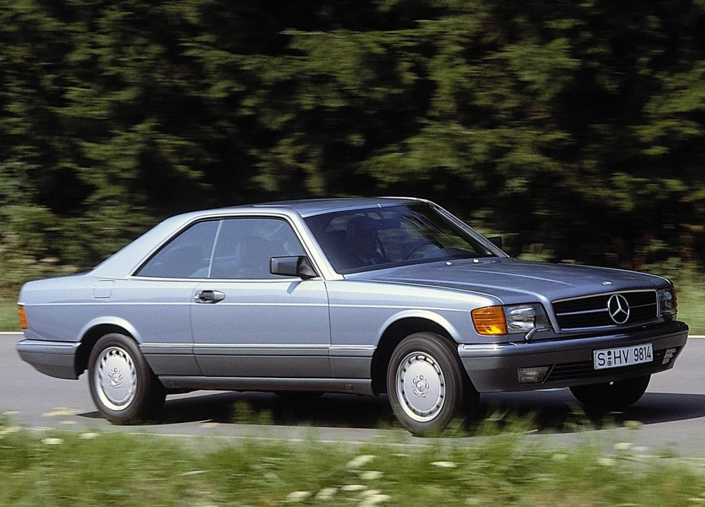 A silver-blue 1981 Mercedes S-Class Coupe drives down a forested road