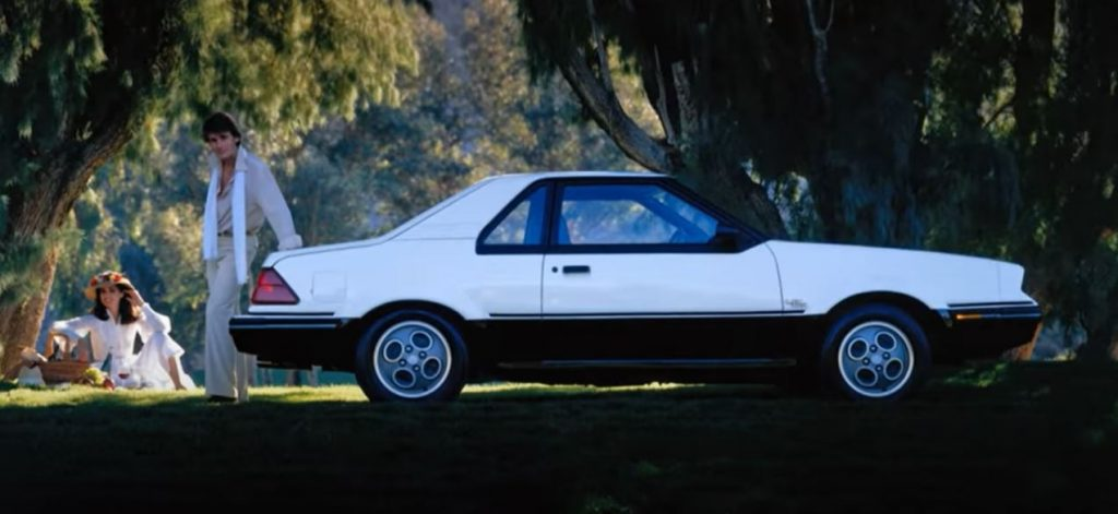 A white-and-black 1982 Ford EXP in a shady forest area