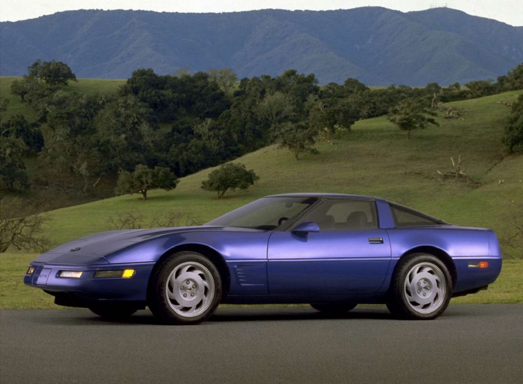 A blue 1983 Chevrolet C4 Corvette in front of some rolling green hills