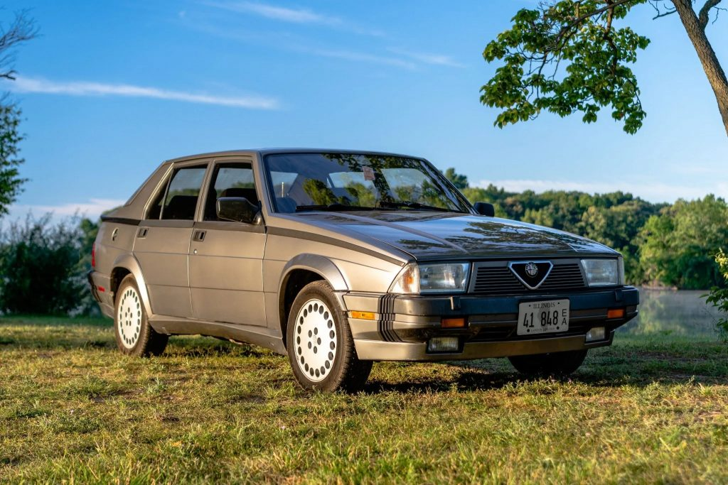 A gray 1988 Alfa Romeo Milano Verde lit by the setting sun