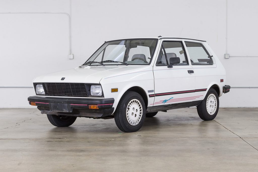 A white, small compact hatchback - the 1989 Yugo