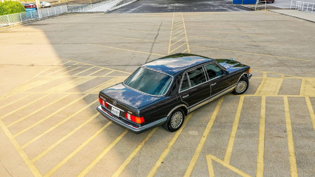 An overhead rear 3/4 view of a black 1991 W126 Mercedes-Benz 560SEL in a parking lot
