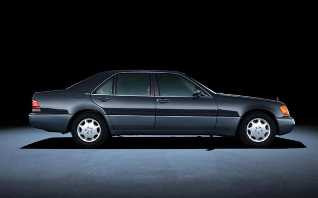 The side view of a black V12-powered 1992 Mercedes-Benz W140 S-Class sedan