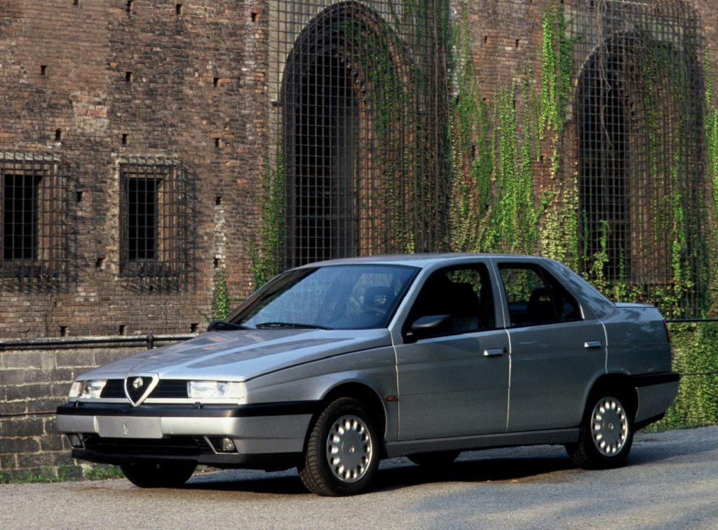 A silver 1993 Alfa Romeo 155 in front of an ivy-covered stone building