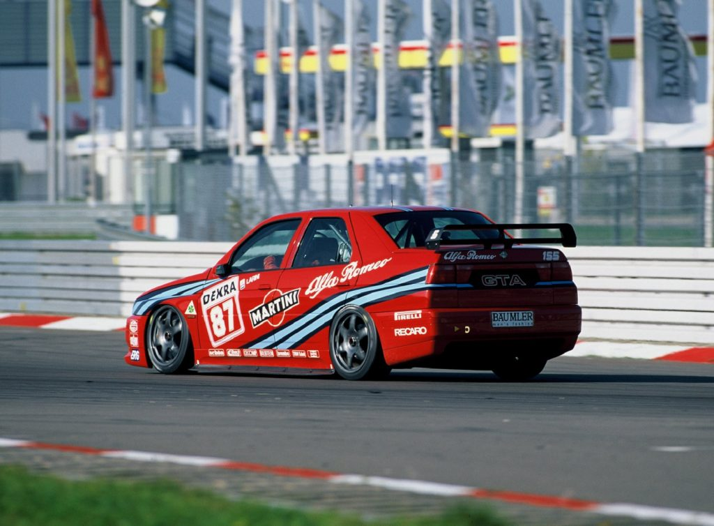 A red 1993 Alfa Romeo 155 2.5 TI DTM race car drives around the track