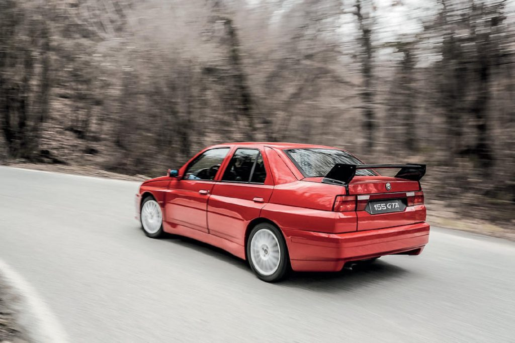 The red 1993 Alfa Romeo 155 GTA Stradale tackles a forested corner