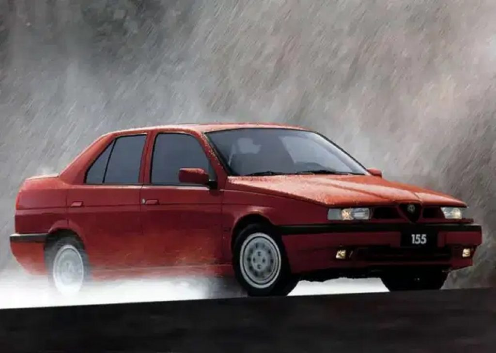 A red 1993 Alfa Romeo 155 Q4 driving through the pouring rain