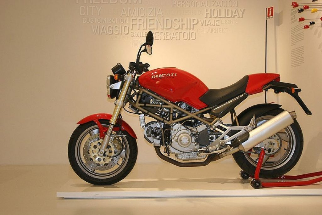 A red 1993 Ducati Monster M900 on a rear-wheel stand in the Ducati museum