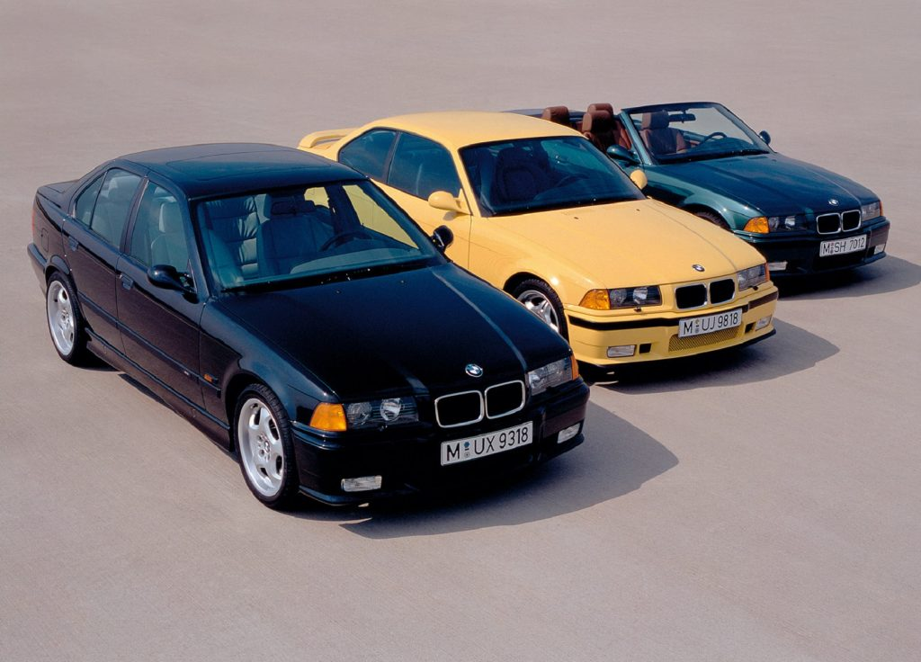 A black 1995 BMW E36 M3 sedan next to a yellow coupe next to a green convertible