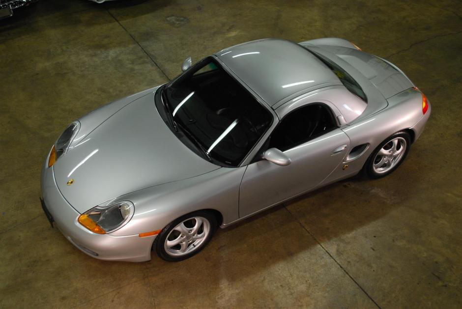 A silver 1997 Porsche Boxster with a hard top sits in the middle of a garage.